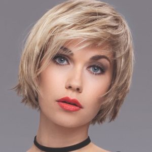 Woman in red lipstick wearing a short blonde razor cut bob wig.