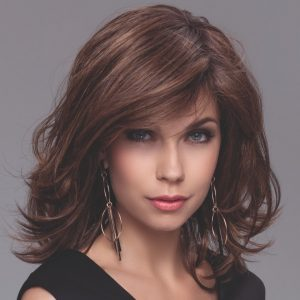 Model wearing a brunette wig with shoulder length layers and side swept fringe.